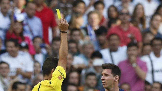"""Barcelona's Messi is shown a yellow card by referee Manzano during the Spanish first division """"Clasico"""" soccer match against Real Madrid at the Santiago Bernabeu stadium in Madrid"""