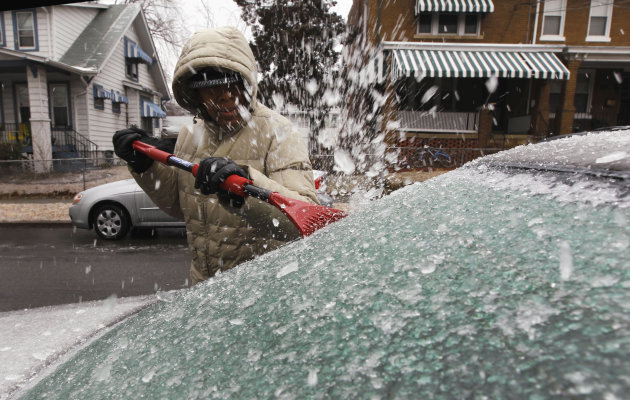 Yvette Judge works to clear the ice from the back window of her car, in Washington, Tuesday, Jan. 18, 2011, after a mix of freezing rain and sleet fell overnight in the Washington area.