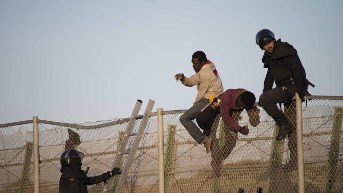 African migrants sit atop a border fence between Morocco and Melilla