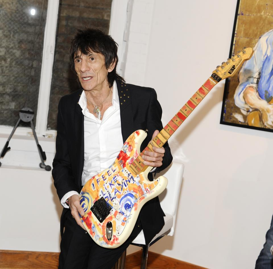 "Rolling Stones guitarist Ronnie Wood holds up one of his works of art during a news conference unveiling his new art exhibit ""Faces, Time and Places"" on Monday, April 9, 2012, in New York. (AP Photo/Evan Agostini)"