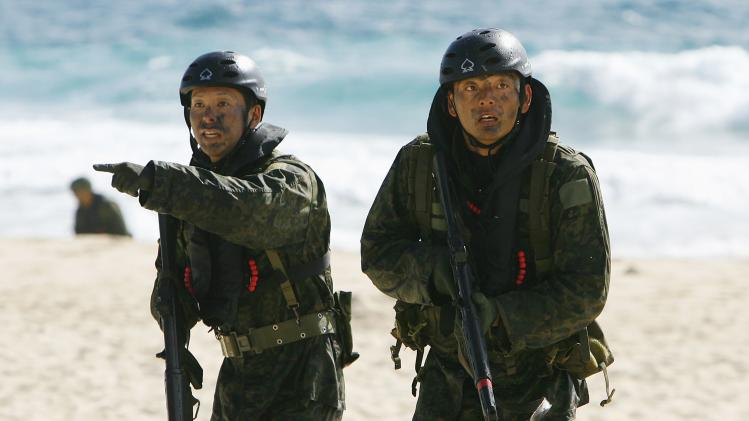 Members of the Japan Maritime Self-Defense Force make their way up the beach while participating in an assault exercise at Marine Corps Base Hawaii during the multi-national military exercise RIMPAC in Kaneohe