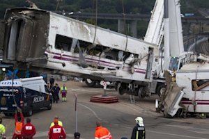 Derailed cars are removed as emergency personnel work …