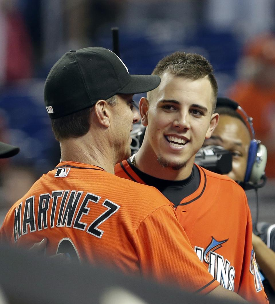 Miami Marlins hitting coach Tino Martinez, left, congratulates pitcher Jose Fernandez, right, after a baseball game against the Pittsburgh Pirates in Miami, Sunday, July 28, 2013. Martinez has resigned after players complained he verbally abused them. (AP Photo/Alan Diaz)