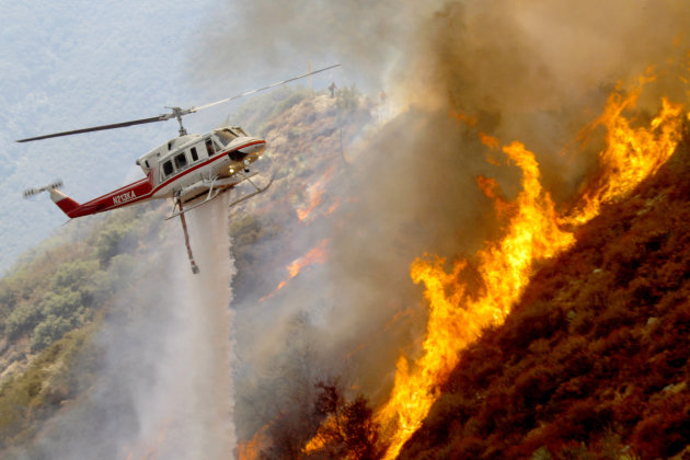 A Los Angeles County Firefighter helicopter drops water on a wildfire burning through 3,600 acres of the Angeles National Forest on Tuesday Sept. 4, 2012 near Glendora, Calif. It could be a week befor