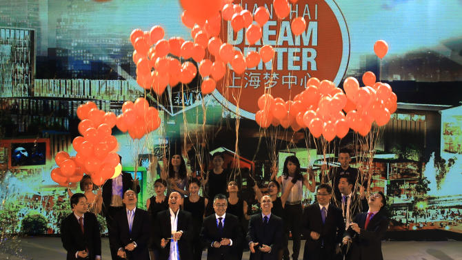 Jeffrey Katzenberg, CEO of DreamWorks Animation, third from right, Li Ruigang, Chairman & CEO of China Media Capital, fourth from right, and Allan Zeman, Chairman of Lan Kwai Fong Group, third from left, together with representatives from the Shanghai government, unveil the master plan for the Shanghai DreamCenter on Thursday March 20, 2014 in Shanghai, China. DreamWorks Animation and Chinese partners unveiled designs on Thursday for a 15 billion yuan ($2.4 billion) entertainment complex in Shanghai, expanding Hollywood's growing ties with China. (AP Photo)