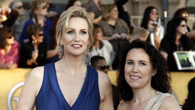 """FILE - In this Jan. 29, 2012, file photo, Jane Lynch, left, and Lara Embry arrive at the 18th Annual Screen Actors Guild Awards in Los Angeles. Lynch is divorcing her wife of three years, Dr. Lara Embry, who she married in 2010 in Massachusetts. She told People magazine in a statement Monday, June 10, 2013, that splitting up was """"a difficult decision for us as we care very deeply about one another."""" (AP Photo/Matt Sayles, File)"""