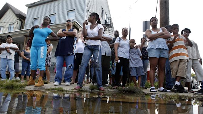 A crowd watches from a street corner Wednesday, Aug. 31, 2011, in Paterson, N.J., as New Jersey Gov. Chris Christie and Department of Homeland Security Secretary Janet Napolitano make a stop on a tour of areas flooded by Hurricane Irene. Later it was announced to the crowd that President Obama had signed a disaster declaration for hard-hit New Jersey after Hurricane Irene left much of  northern New Jersey flooded. (AP Photo/Mel Evans, Pool)