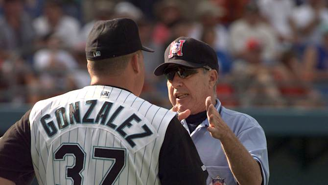 ILE - In this May 31, 1999, file photo, Florida Marlins manager Freddi Gonzalez, left, listens to third base umpire Frank Pulli during the fifth inning of a baseball game against the St. Louis Cardinals in Miami. Pulli used instant TV replay to retract a home run call, turning it into a double, given to Marlins' Cliff Floyd. Longtime major league umpire Pulli, who used instant replay to make a call well before it was allowed, has died. He was 78. (AP Photo/Tony Gutierrez, File)