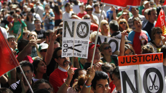 "People hold up banners reading ""their fortune, our crisis"", ""no food, no peace"" and ""no cuts!, justice"" during a protest against austerity measures applied by the Spanish government in  olumbus Square, Madrid, Spain, Saturday, Sept. 15, 2012. Tens of thousands of people from all over the country converged on Madrid to hold a large anti-austerity demonstration on Saturday. (AP Photo/Andres Kudacki)"