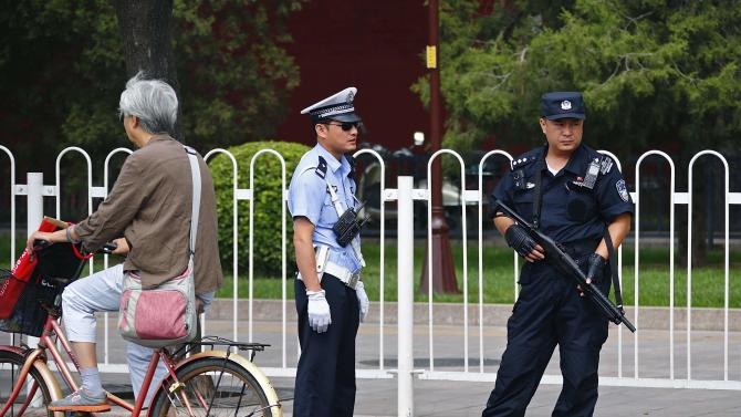 A resident rides a bicycle past armed policemen who are standing guard on Chang'an Avenue in Beijing