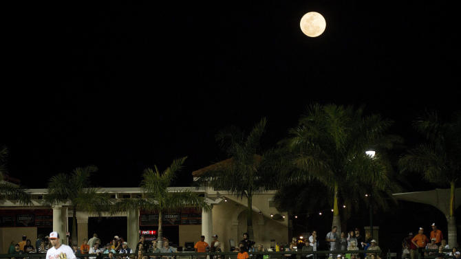 The moon rises as the Baltimore Orioles get set to play against Toronto Blue Jays during an exhibition baseball game Thursday, March 5, 2015 in Sarasota, Fla. (AP Photo/The Canadian Press, Nathan Denette)