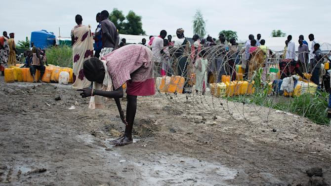 A girl washes her feet with standing water on August 1, 2014 next to a watering point at the UN Protection of Civilians (PoC) site in Upper Nile State capital Malakal, South Sudan