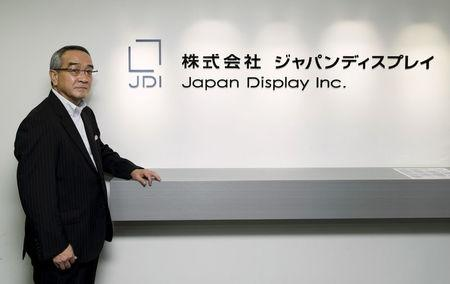 Homma poses in front of the company's logo at its headquarters in Tokyo