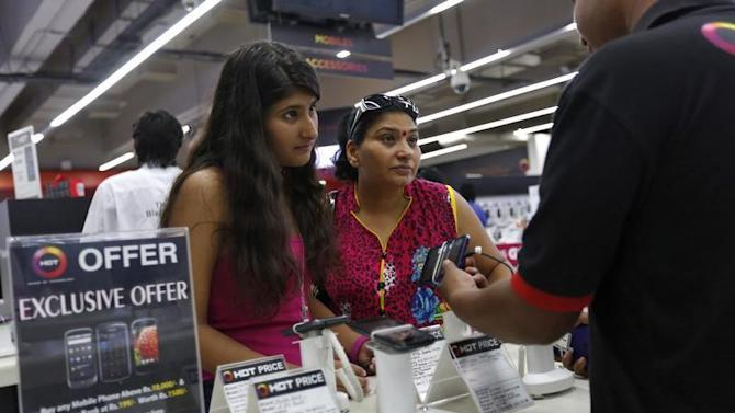 An employee demonstrates a mobile phone to customers at an electronics store in New Delhi