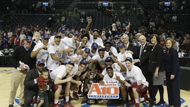 Saint Joseph's players, along with supporters and officials, pose with the championship trophy after an NCAA college basketball game against VCU in the championship round of the Atlantic 10 Conference tournament at the Barclays Center in New York, Sunday, March 16, 2014. St. Joseph's defeated VCU 65-61