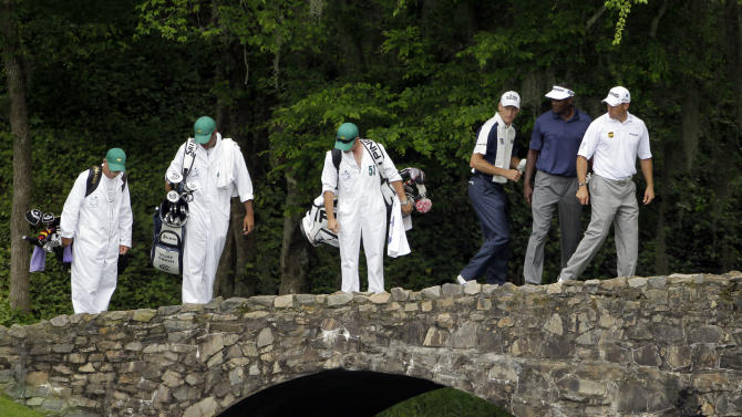 From right, Lee Westwood, of England, Vijay Singh, of Fiji, and Jim Furyk and their caddies look over the edge of the Ben Hogan Bridge on the 12th hole during the first round of the Masters golf tournament Thursday, April 5, 2012, in Augusta, Ga. (AP Photo/Darron Cummings)