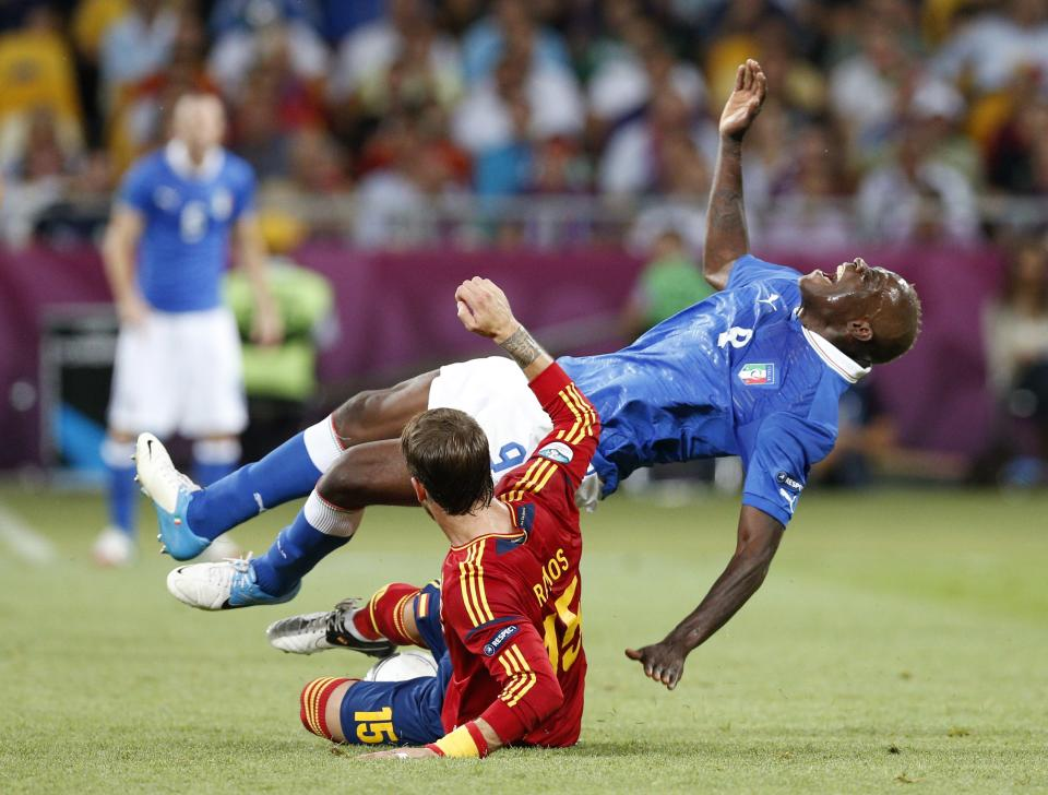 Italy's Mario Balotelli, top, is fouled by Spain's Sergio Ramos during the Euro 2012 soccer championship final  between Spain and Italy in Kiev, Ukraine, Sunday, July 1, 2012. (AP Photo/Michael Sohn)