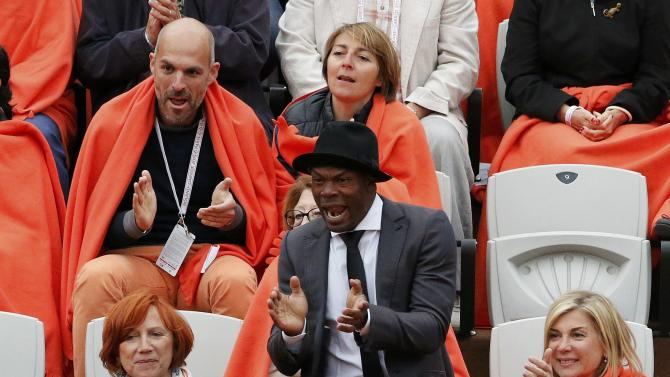 French actress Michele Laroque (R) and Former France's soccer player Sylvain Wiltord watch the men's singles match between Gael Monfils of France and Pablo Cuevas of Uruguay at the French Open tennis tournament at the Roland Garros stadium in Paris