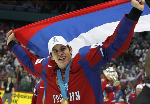 Russia's Malkin holds a national flag as he celebrates winning their 2012 IIHF men's ice hockey World Championship final game against Slovakia in Helsinki