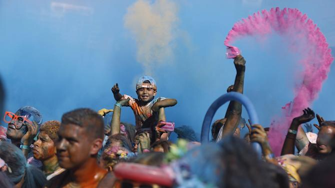 Participants celebrate amid colored powder while taking part in the Color Run race in Tegucigalpa