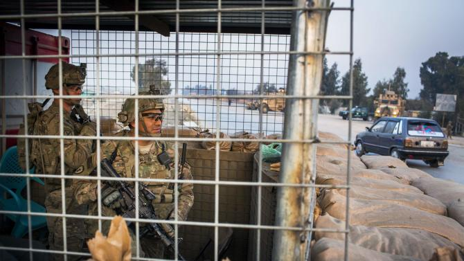 U.S. soldiers from Grim Company of the 3rd Cavalry Regiment watch over a street from inside of an Afghan police checkpoint during a mission near Forward Operating Base Fenty in the Nangarhar province of Afghanistan