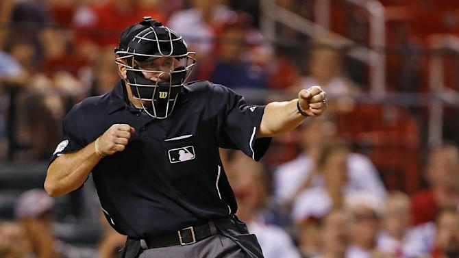 Home plate umpire Mike Muchlinski makes a strike three call during a baseball game between the St. Louis Cardinals and the Cincinnati Reds, Wednesday, July 29, 2015, in St. Louis. (AP Photo/Billy Hurst)