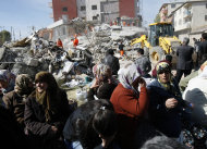 People wait for word from their family members as rescuers work to save people from debris in Ercis, Van, eastern Turkey, Monday, Oct. 24, 2011. A survivor of the 7.2-magnitude quake that has killed at least 239 people in eastern Turkey was pulled from the rubble with three other people on Monday after he managed to call for help on his cell phone. Dozens of people were trapped in hills of debris, but authorities offered hope that the death toll may not rise as high as initially feared.(AP Photo/Burhan Ozbilici)