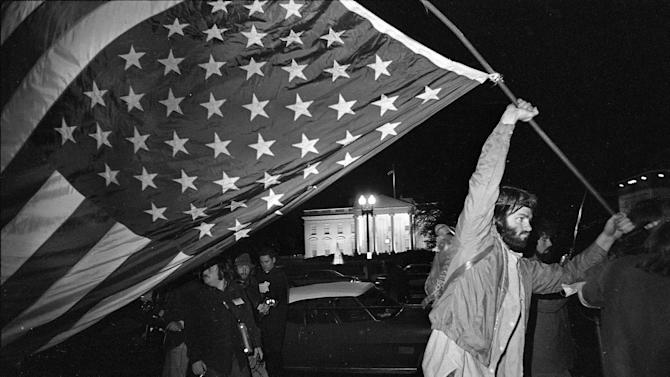 FILE - In this April 22, 1971 file photo, a demonstrator carries an inverted flag, a symbol of distress, as protesters against the Vietnam War march past the White House from their encampment on the Mall. (AP Photo/Henry Burroughs)