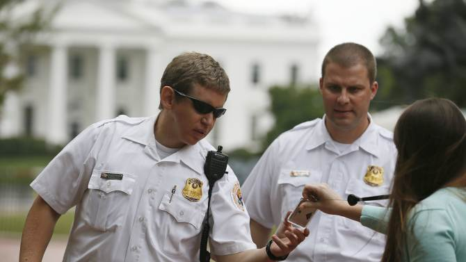 U.S. Secret Service Uniformed Division officers check the identification badge of a person wishing to approach the White House during the visit of Israel's PM Netanyahu in Washington