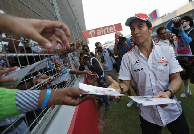 McLaren F1 driver Perez distributes his autographs to fans at the Buddh International Circuit in Greater Noida