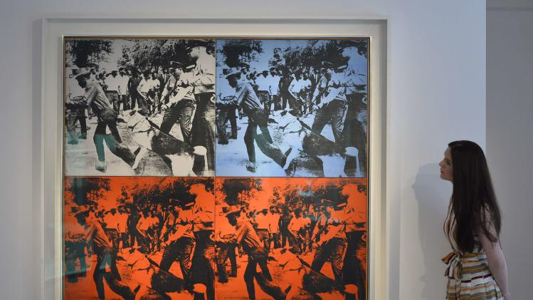 A Christie's employee poses next to 'Race Riot' by U.S. artist Andy Warhol at Christie's auction house in central London