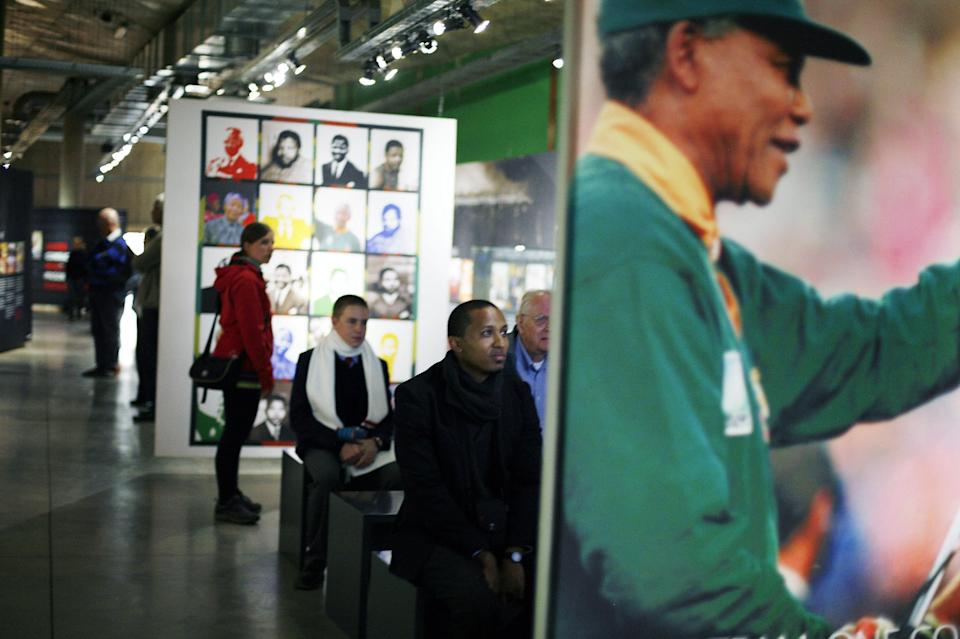 Tourists visit a temporary exhibit on Nelson Mandela at the Apartheid Museum in Johannesburg Tuesday June 11, 2013. Former South African President Nelson Mandela is spending a fourth day in a hospital, where he is being treated for a recurring lung infection. (AP Photo/Jerome Delay)