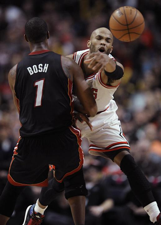 Chicago Bulls' Taj Gibson (22), slaps the ball away from Miami Heat's Chris Bosh (1), during the fourth quarter of an NBA basketball game in Chicago, Sunday, March 9, 2014. Chicago won 95-88 i