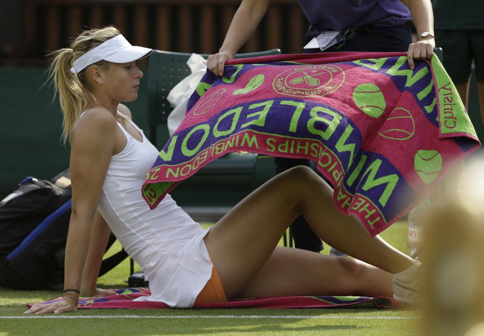Maria Sharapova of Russia is attended to by a physiotherapist during her Women's second round singles match against Michelle Larcher De Brito of Portugal at the All England Lawn Tennis Championships in Wimbledon, London, Wednesday, June 26, 2013. (AP Photo/Anja Niedringhaus)