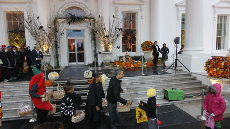 President Barack Obama first lady Michelle Obama and mother-in-law Marian Robinson hand out Halloween treats as they welcome children from the Washington area and military members and their families to trick-or-treat at the White House in Washington, Saturday, Oct., 29, 2011. (AP Photo/Pablo Martinez Monsivais)
