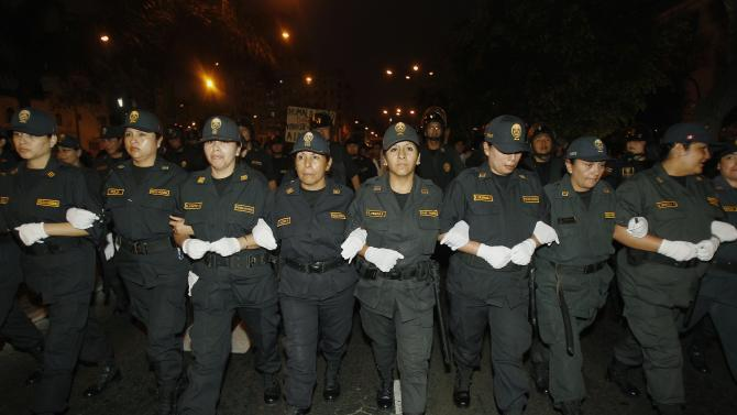 Riot police officers link hands to form a line during an anti-government demonstration in Lima