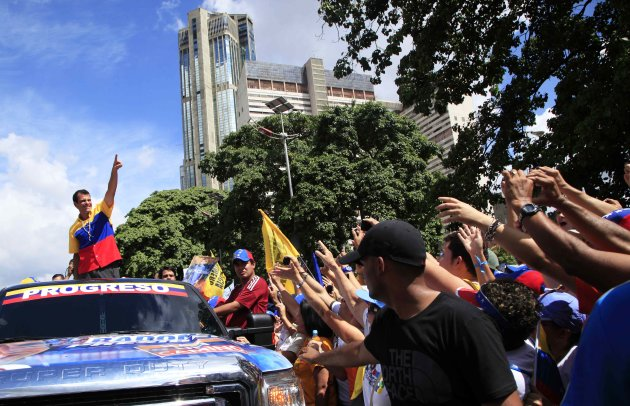 Opposition presidential candidate Henrique Capriles, top, gestures to supporters during a campaign rally in Caracas, Venezuela, Sunday, Sept. 30, 2012. Presidential elections in Venezuela are scheduled for Oct. 7. (AP Photo/Ariana Cubillos)
