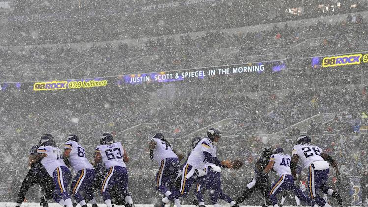 Snow falls as Minnesota Vikings quarterback Matt Cassel, center, prepares to hand the ball off to running back Adrian Peterson (28) in the first half of an NFL football game against the Baltimore Ravens, Sunday, Dec. 8, 2013, in Baltimore