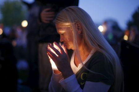 A woman takes part in a candlelight vigil for victims of the Umpqua Community College shooting, in Winston