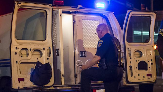 A policeman opens the back of a police van to load those detained for defying a curfew in west Baltimore