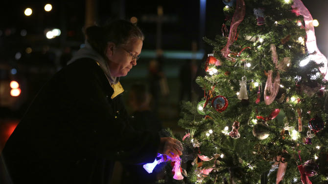 Kelly Borel, of Waterloo, Iowa, puts an ornament on a tree during a vigil for missing cousins Lyric Cook, 10, and Elizabeth Collins, 8, who vanished while riding bikes in Evansdale in July, Thursday, Dec. 6, 2012, in Evansdale, Iowa. Authorities announced Thursday they are confident bodies found in an isolated wildlife area are those of the two girls. (AP Photo/Charlie Neibergall)