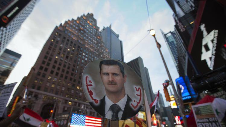 Local activists and Syrian-American supporters of Syrian President al-Assad hold up his image during anti-war rally in front of U.S. Armed Forces Recruiting Station in Times Square, New York