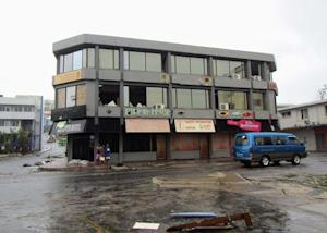 A damaged building and debris can be seen on a road…