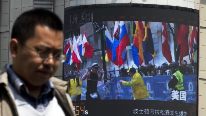 A Chinese man walks past a huge screen which reports Boston Marathon bombings that killed three and wounded more than 170 people, in Beijing, China Wednesday, April 17, 2013. A state-run Chinese newspaper says the third person killed in the Boston Marathon bombings is a Chinese graduate student at Boston University originally from China's northeastern city of Shenyang. (AP Photo/Andy Wong)