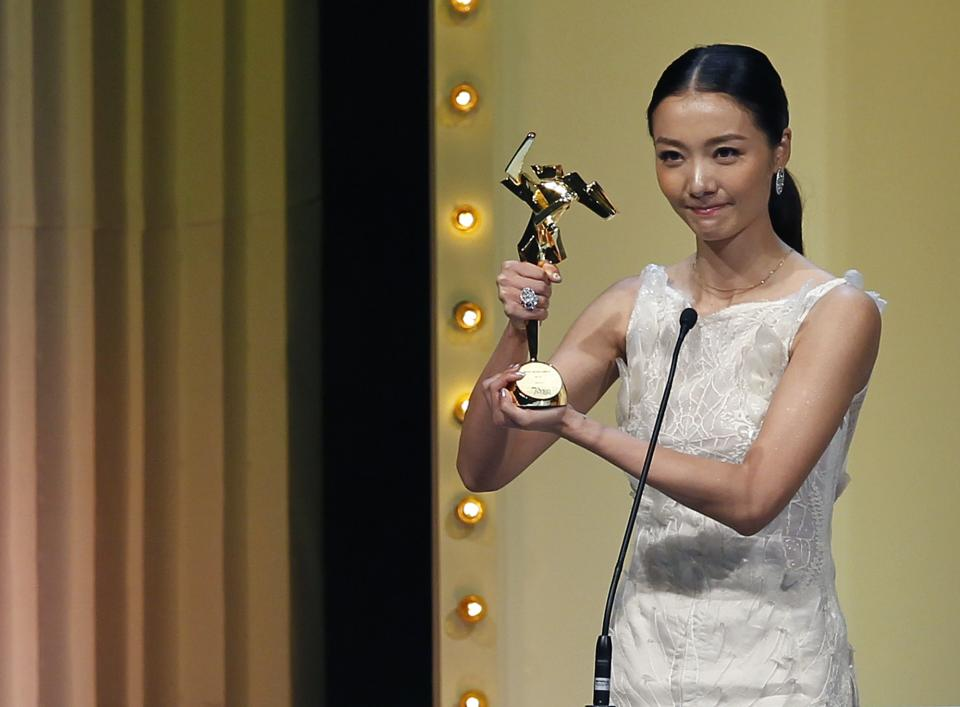 "Chinese actress Qi Xi gestures after she receives the Best Newcomer award for the film "" Mystery ""at the Asian Film Awards in Hong Kong Monday, March 18, 2013. (AP Photo/Vincent Yu)"