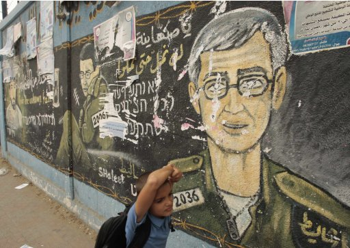 A Palestinian schoolboy walks past a mural depicting captured Israeli soldier Gilad Shalit in the Gaza Strip