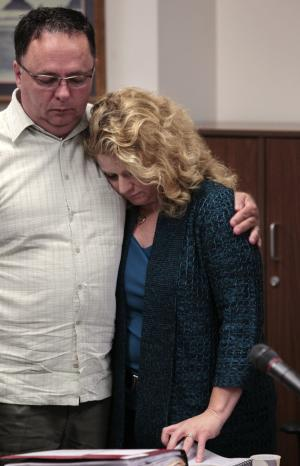 ADDS NAME OF MAN - Trisha Conlon, right, is embraced by her husband Bill Conlon  following a court hearing Thursday, Aug. 25, 2011, in Seattle. Conlon was in court in another attempt to keep her two sons from living with her ex-husband's wife, a woman who killed her own daughters 20 years ago. Conlon has two teenage boys from her marriage with John P. Cushing Jr. After they split up, Cushing got back together with his first wife, Kristine, even though Kristine had killed their 4- and 8-year-old girls at their home in California's Orange County in 1991. (AP Photo/Elaine Thompson)