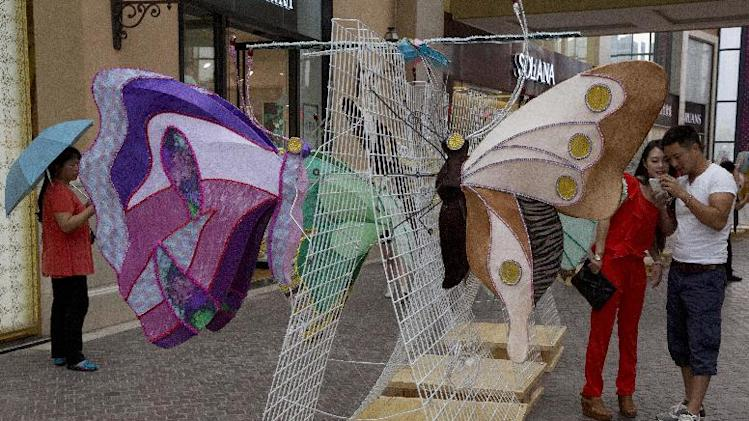 A woman looks at photos with her partner after posing with butterfly installations at a mall in Beijing, China, Thursday, Aug. 28, 2014. Mall operators routinely display art works to increase the flow of visitors as a way to boost sales of retail tenants. (AP Photo/Ng Han Guan)