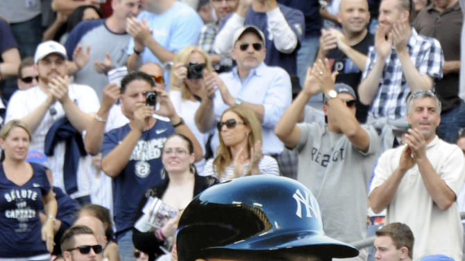A fan holds up a picture of New York Yankees' Derek Jeter as he comes to bat during the first inning of a baseball game against the Toronto Blue Jays Saturday, Sept. 20, 2014, at Yankee Stadium in New York. (AP Photo/Bill Kostroun)