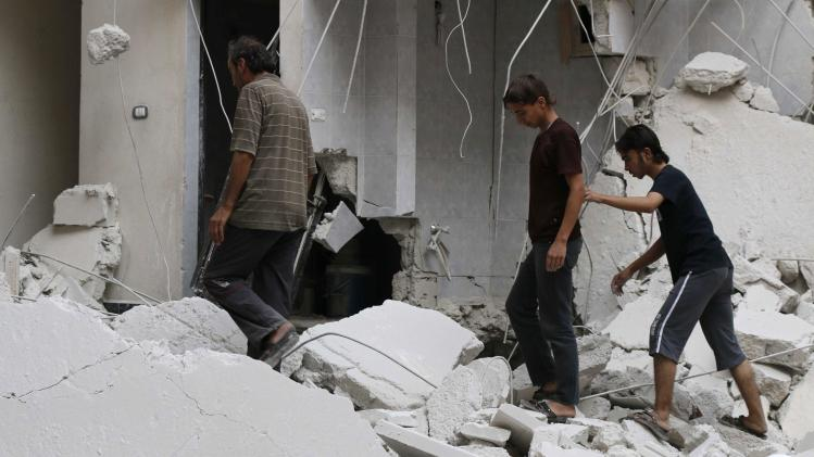People walk at a site hit by what activists said was a barrel bomb dropped by forces loyal to Syria's President Bashar al-Assad, in the Al-Fardous neighbourhood of Aleppo
